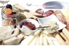 Particolare dell'aperitivo con formaggi misti, pomodori secchi e salsa